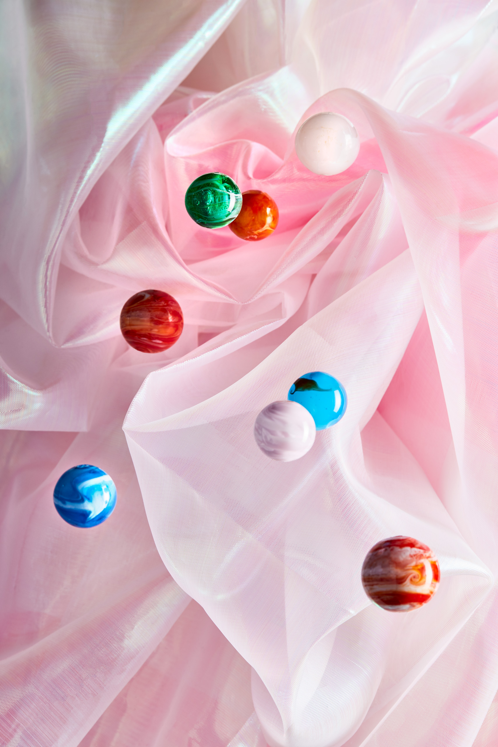 Glass planets against pink fabric